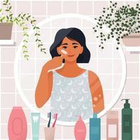 mujer en el espejo, en el baño, haciendo masaje facial vector