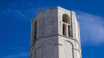 La torre de una iglesia católica en Italia con fondo de cielo azul foto