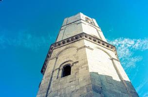 La torre de una iglesia medieval católica en Italia con una ventana foto