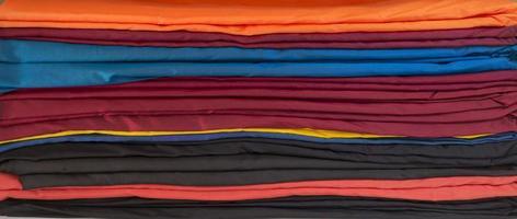 una pila horizontal de tela doblada de diferentes colores foto