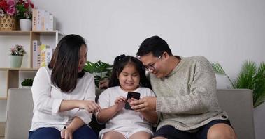 père et mère se joignent à leur fille jouant sur un smartphone video