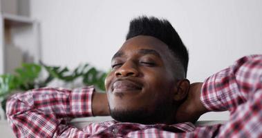 calmo e sorridente jovem relaxa no sofá video