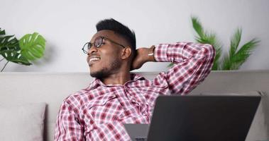 Hombre feliz relajarse mirando a otro lado soñando mientras usa el portátil video