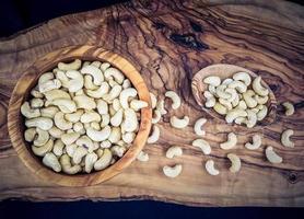 un montón de anacardos en madera de olivo foto