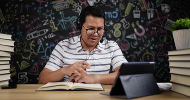 El hombre usa auriculares y una tableta para enseñar en línea. video