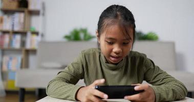 niña juega en el teléfono inteligente video