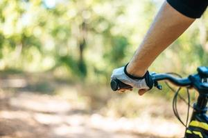 Mountain cyclists grasp the bike handle, focus on gloves photo