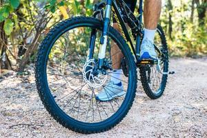 una perspectiva de ciclistas en un camino rocoso que se centra en las ruedas de los coches. foto