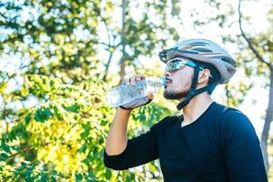 Cyclists stand on the top of the mountain and drink a bottle of water. photo