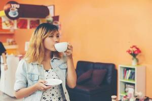 Young beautiful woman drinking hot cappuccino coffee at cafe. photo