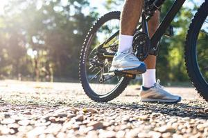 A low perspective of mountain cyclists on a rocky path Focus on shoes photo