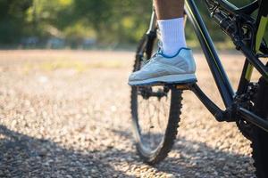 Una baja perspectiva de los ciclistas de montaña en un camino rocoso se centran en los zapatos foto