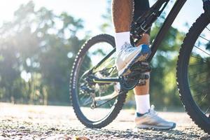 Una perspectiva ciclistas en un camino rocoso al atardecer se centran en los zapatos foto