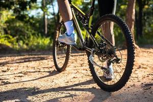 una perspectiva ciclistas en un camino rocoso que se centra en las ruedas del coche. foto