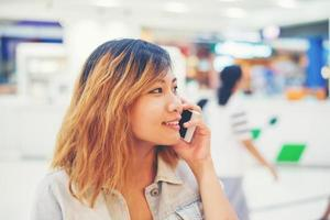 Beautiful young woman talking on the phone in the shopping mall. photo