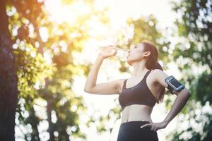 Fitness woman athlete takes a break, Drinking water, Hot day. photo