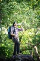 joven excursionista relajándose en la cima de una montaña, disfruta de la naturaleza y la aventura. foto
