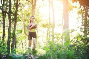 mujer joven para correr en un camino rural en la naturaleza del bosque verde. foto
