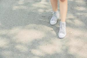 Woman feets walking on the road in the park photo