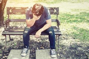 hombre de dolor de cabeza sentado en un banco. foto