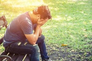hombre de dolor de cabeza sentado en un banco en el parque. foto