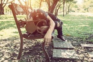 Joven durmiendo en un banco al aire libre en el parque de la ciudad durante el día foto