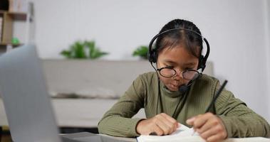 niña estudiando en línea con auriculares en casa video