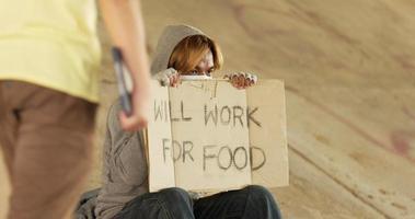 Hombre sin hogar sosteniendo trabajará para signo de comida video
