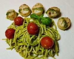 Fried saltwater seashells on spaghetti with green pesto photo