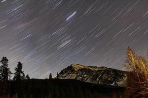 Estelas de estrellas sobre las Montañas Rocosas. Parque Nacional Jasper, Alberta, Canadá foto
