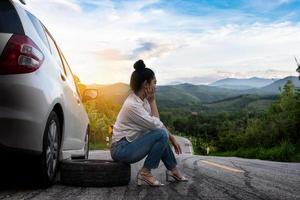 Young beautiful lady sit near car for calling for help photo