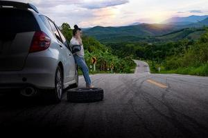Young beautiful lady standing near car for calling for help photo