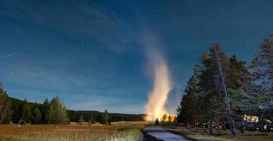 Eruption of Old Faithful geyser at Yellowstone National Park at night photo
