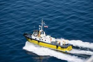 Barco piloto que conduce gran barco a través de las aguas. foto