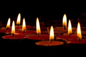 Flaming candles on black photo