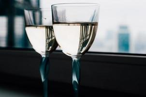 Two glasses of white wine on the window sill, beautiful reflections photo