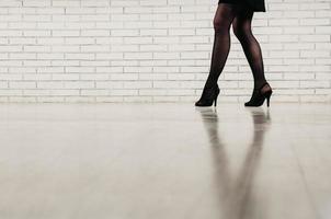 Piernas de una mujer vestida con medias negras y zapatos de tacón alto foto