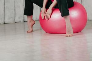 A girl sitting on a pink fit ball in a gym, light background photo