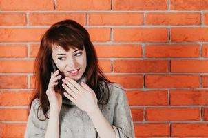 Pretty woman talking by cellphone, smiling, brick wall in the backdrop photo