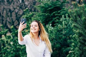 Una mujer joven y bonita sonriendo y haciendo selfie en un parque foto