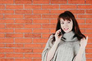 Pretty girl talking by cellphone, surprisingly smiling, gray pullover photo