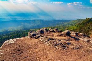 acantilado de piedra de tailandia con rayos de sol y fondo de montaña foto