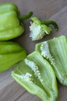 pimientos morrones, cortados en mitades y enteros. verduras frescas para cocinar foto