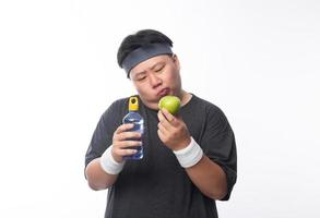 joven asiático gordo elegir manzana verde foto