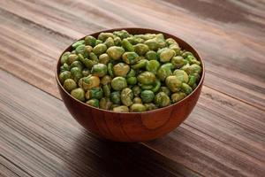 Salted green peas in wooden bowl on the table, Healthy snack photo