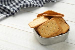 Cracker cookies in a stainless steel bowl with tablecloth photo