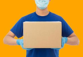 Repartidor con máscara y sosteniendo la caja. foto
