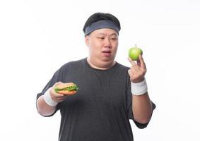 joven gordo elige manzana verde foto