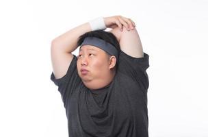 Joven asiático divertido hombre de deporte gordo estiramiento antes del ejercicio foto