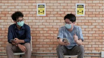 Two Asian men wearing face masks sit socially distancing. video
